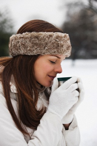 Young woman wearing a fur headband holding a hot drink