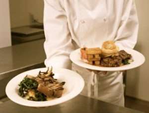 chef holding plated dinners