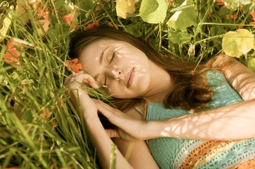 Woman napping in grass and flowers Discover: Summer Naps EAT LOVE SAVOR International luxury lifestyle magazine and bookazines