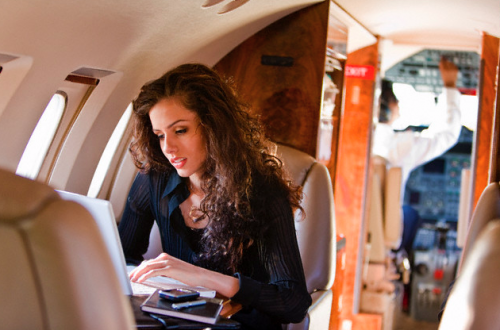 woman looking at computer on luxury jet SocialLuxe: List of Luxury Brands on Twitter - EAT LOVE SAVOR International luxury lifestyle magazine and bookazines