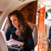 woman looking at computer on luxury jet